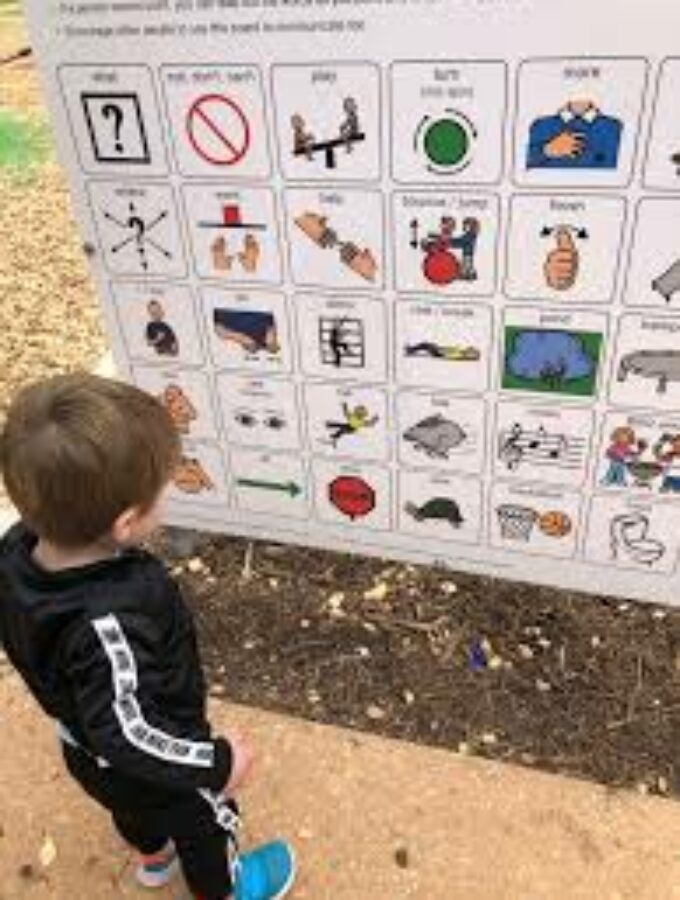 Young boy standing in front of the playground board