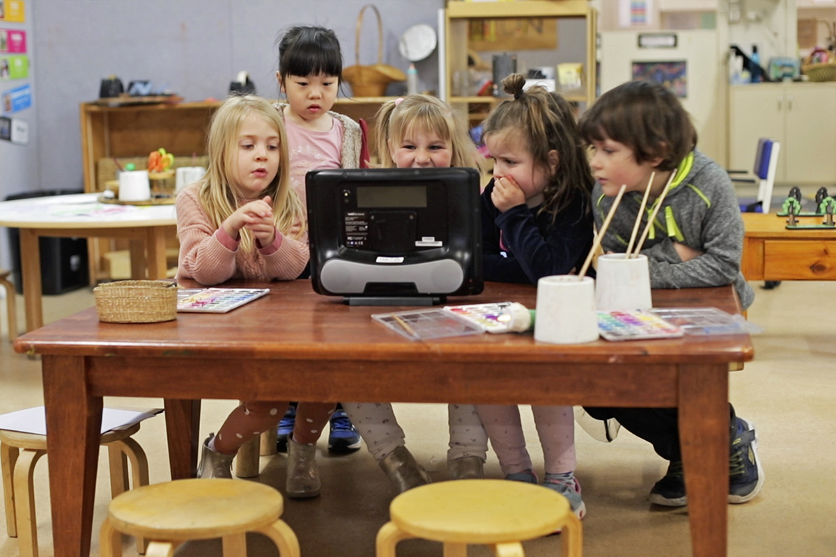 Young children gathered around a desk looking at a screen