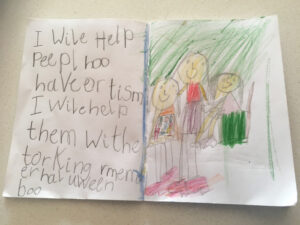 "A child's picture with the text ""I will help people who have Autism. I will help them with the talking. Remember Halloween - Boo"" (The end of the message was distracted by her upcoming Halloween celebrations). The picture shows her helping her mum at work by holding a PODD communication book."